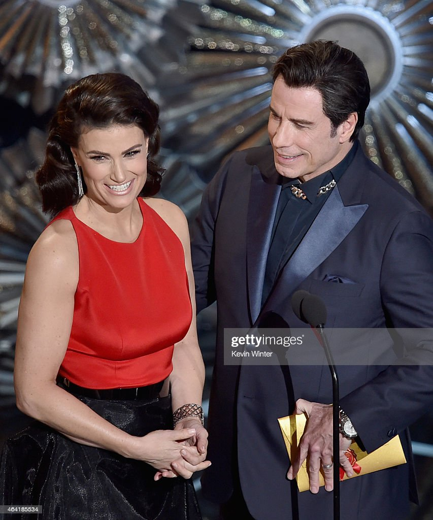 Actress <a gi-track='captionPersonalityLinkClicked' href=/galleries/search?phrase=Idina+Menzel&family=editorial&specificpeople=213583 ng-click='$event.stopPropagation()'>Idina Menzel</a> and actor <a gi-track='captionPersonalityLinkClicked' href=/galleries/search?phrase=John+Travolta&family=editorial&specificpeople=178204 ng-click='$event.stopPropagation()'>John Travolta</a> speak onstage during the 87th Annual Academy Awards at Dolby Theatre on February 22, 2015 in Hollywood, California.