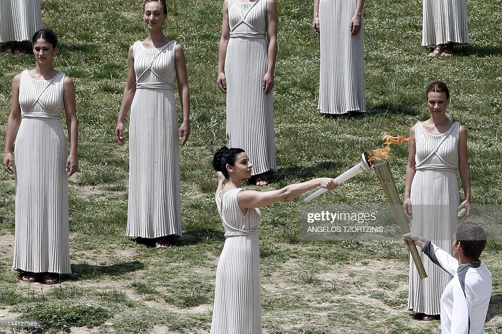 Actress Ino Menegaki, acting as high priestess, passes the Olympic flame to the first torch bearer, swimmer Spyros Gianniotis on May 10, 2012 during the lighting ceremony at the ancient site of Olympia the sanctuary where the Olympic Games were born in 776 B.C. The ceremony marks the start of a week-long torch relay, which will take it to five major Greek archaeological sites, including the Acropolis, before it arrives at the old Olympic stadium in Athens, site of the first modern Games in 1896. AFP PHOTO / Angelos Tzortzinis