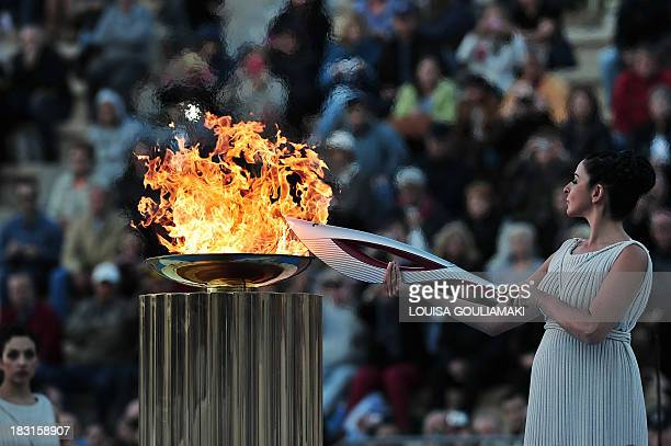 Actress Ino Menegaki plays a high priestess as she lights a torch with the Olympic flame on October 5 2013 at the Panathenaic stadium in Athens...