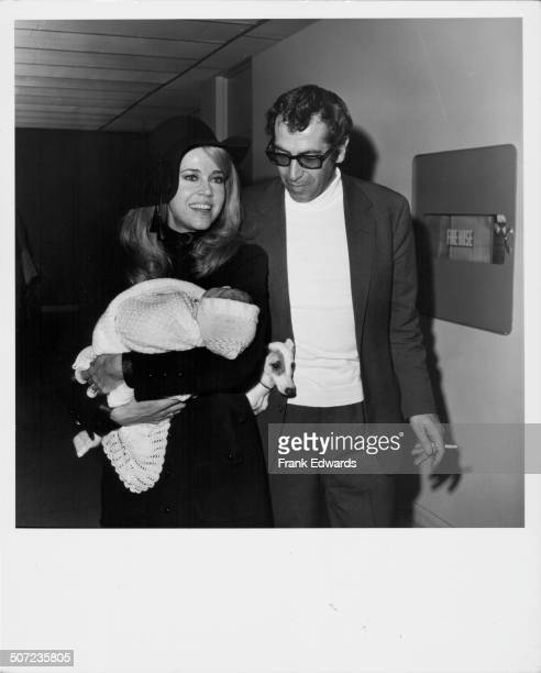 Actress Jane Fonda and her husband Roger Vadim holding their baby and a dog as they walk through Los Angeles Airport California 1968