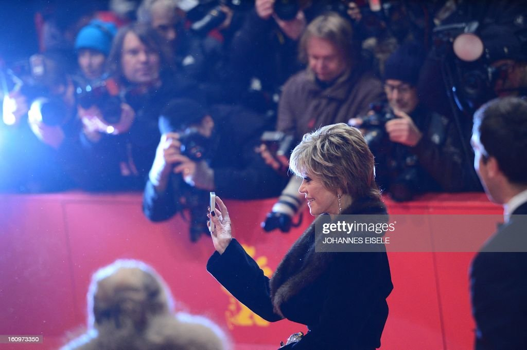 US actress Jane Fonda holds her mobile phone as she walks on the red carpet before a film screening at the 63rd Berlinale Film Festival on February 8, 2013. Guest attended the premiere screening of US director Gus van Sant's film 'Promised'. EISELE