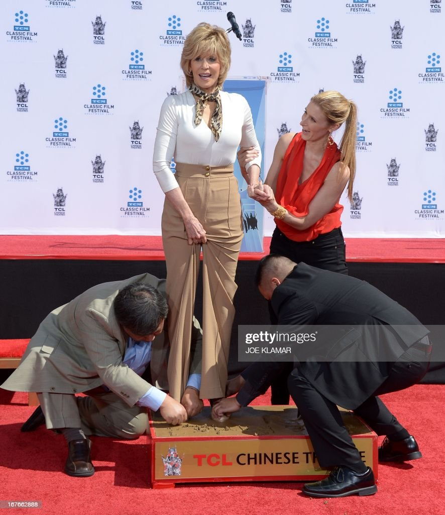 Actress Jane Fonda prints her feet in wet cement during her Handprint/Footprint Ceremony during the 2013 TCM Classic Film Festival at TCL Chinese Theatre on April 27, 2013 in Los Angeles. Fonda is an American actress, writer, political activist, former fashion model, and fitness guru. She rose to fame in the 1960s with films such as Barbarella and Cat Ballou. She has won two Academy Awards, an Emmy Award, three Golden Globes and received several other movie awards and nominations during more than 50 years as an actress. After 15 years of retirement, she returned to film in 2005 with Monster-in-Law, followed by Georgia Rule two years later. She also produced and starred in over 20 exercise videos released between 1982 and 1995, and once again in 2010. AFP PHOTO/JOE KLAMAR