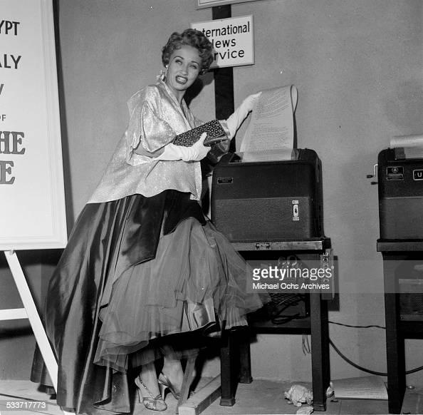 Actress Jane Powell poses with the International News Wire Service machine as she attends the premiere of 'Knights of the Round Table' in Los...