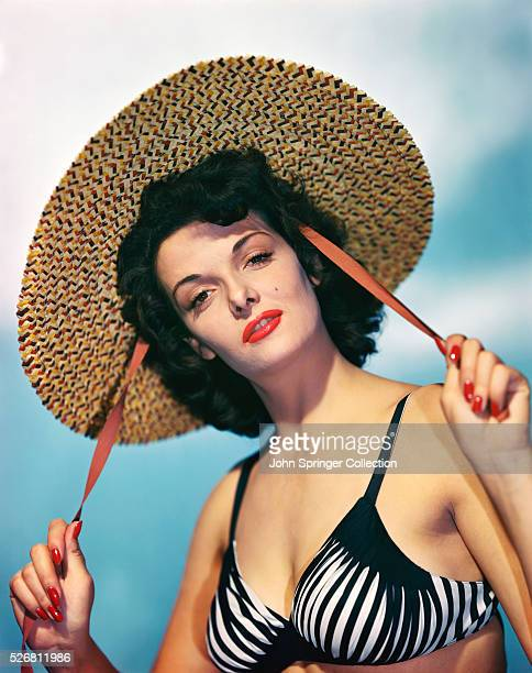 Actress Jane Russell wearing a black and white bikini top while holding the red draw strings of a wide brim straw hat Color publicity handout slide...