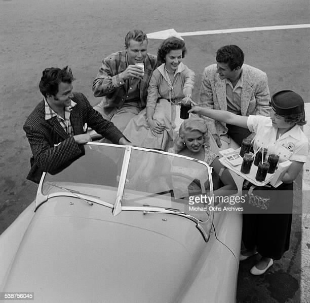 Actress Jayne Mansfield actor Lance Fuller actor John Smith actress Natalie Wood and actor Bob Fuller get Coca Cola's as they pose at a drivein...