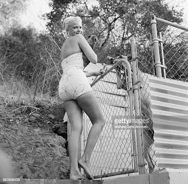 Actress Jayne Mansfield holds a puppy as she gets ready for a photo shoot in a pool in Los AngelesCalifornia