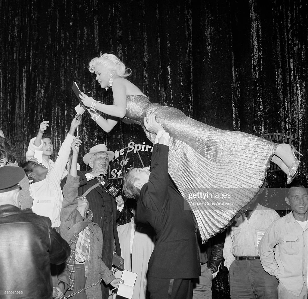 Actress <a gi-track='captionPersonalityLinkClicked' href=/galleries/search?phrase=Jayne+Mansfield&family=editorial&specificpeople=91204 ng-click='$event.stopPropagation()'>Jayne Mansfield</a> is lifted by <a gi-track='captionPersonalityLinkClicked' href=/galleries/search?phrase=Mickey+Hargitay&family=editorial&specificpeople=233644 ng-click='$event.stopPropagation()'>Mickey Hargitay</a> as she signs her autograph as they attend the premiere of 'Sprit of St Louis' in Los Angeles,California.