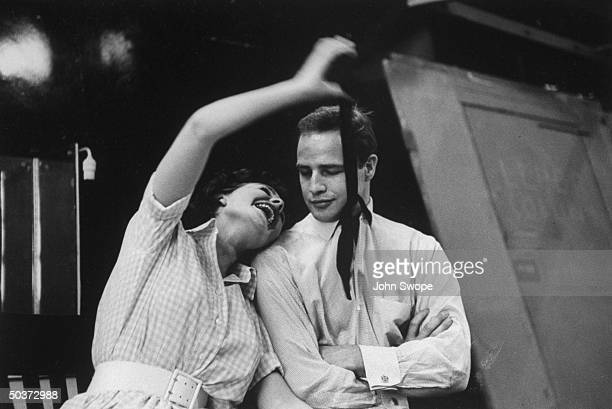 Actress Jean Simmons playfully grabbing Marlon Brando's tie on the set during filming of Guys and Dolls