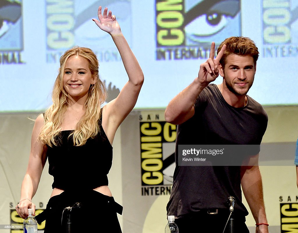 Actress Jennifer Lawrence and actor Liam Hemsworth wave at the audience at the 'The Hunger Games Mockingjay Part 2' panel during ComicCon...