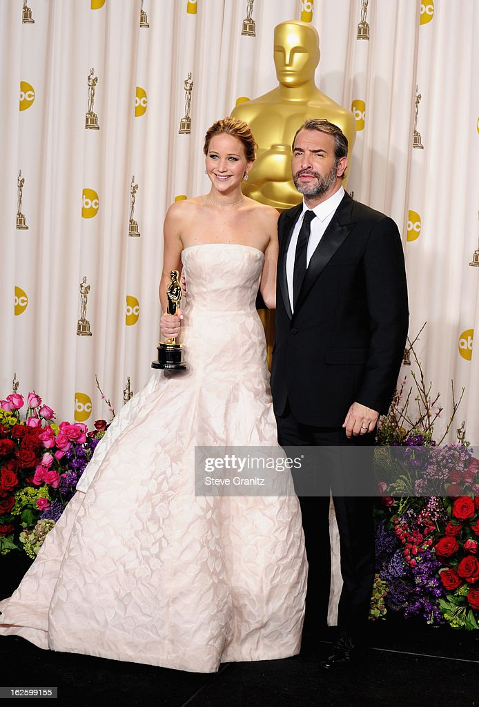Actress Jennifer Lawrence (L) and presenter Jean Dujardin pose in the press room during the Oscars at the Loews Hollywood Hotel on February 24, 2013 in Hollywood, California.