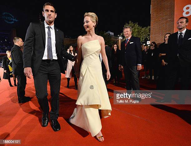 Actress Jennifer Lawrence is lead by a bodyguard during the 'The Hunger Games Catching Fire' Premiere during The 8th Rome Film Festival at Auditorium...