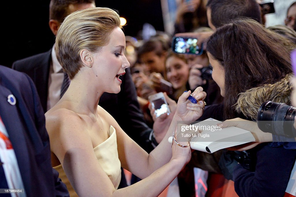 Actress Jennifer Lawrence signs autographs as she attends the 'The Hunger Games Catching Fire' Premiere during The 8th Rome Film Festival at...