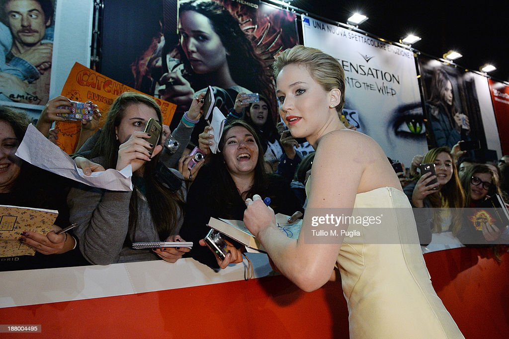 Actress Jennifer Lawrence signs autographs posters for fans during the 'The Hunger Games Catching Fire' Premiere during The 8th Rome Film Festival at...