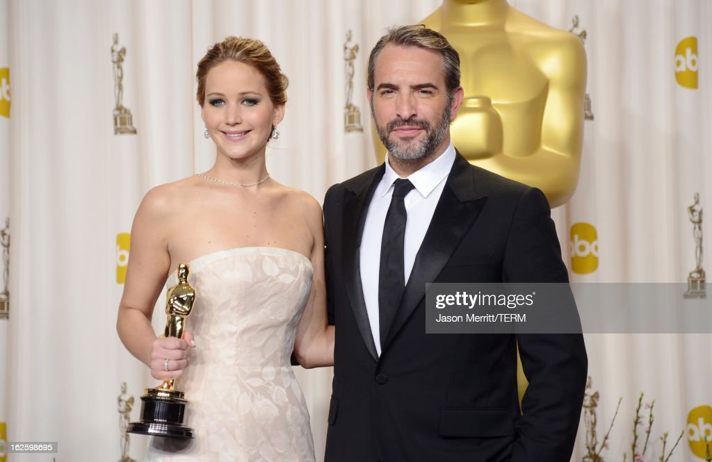 Actress Jennifer Lawrence, winner of the Best Actress award for 'Silver Linings Playbook,' and presenter Jean Dujardin pose in the press room during the Oscars held at Loews Hollywood Hotel on February 24, 2013 in Hollywood, California.