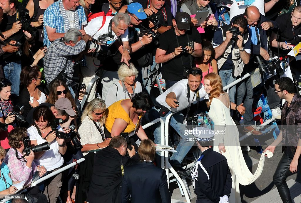 US actress Jessica Chastain poses with a fan on May 21, 2013 as she arrives for the screening of the film 'Cleopatra' presented in Cannes Classics at the 66th edition of the Cannes Film Festival in Cannes. Cannes, one of the world's top film festivals, opened on May 15 and will climax on May 26 with awards selected by a jury headed this year by Hollywood legend Steven Spielberg.