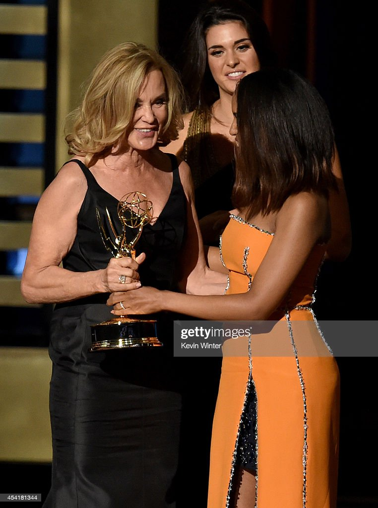 Actress Jessica Lange (L) accepts Outstanding Lead Actress in a Miniseries or Movie for 'American Horror Story: Coven' from actress Kerry Washington onstage at the 66th Annual Primetime Emmy Awards held at Nokia Theatre L.A. Live on August 25, 2014 in Los Angeles, California.
