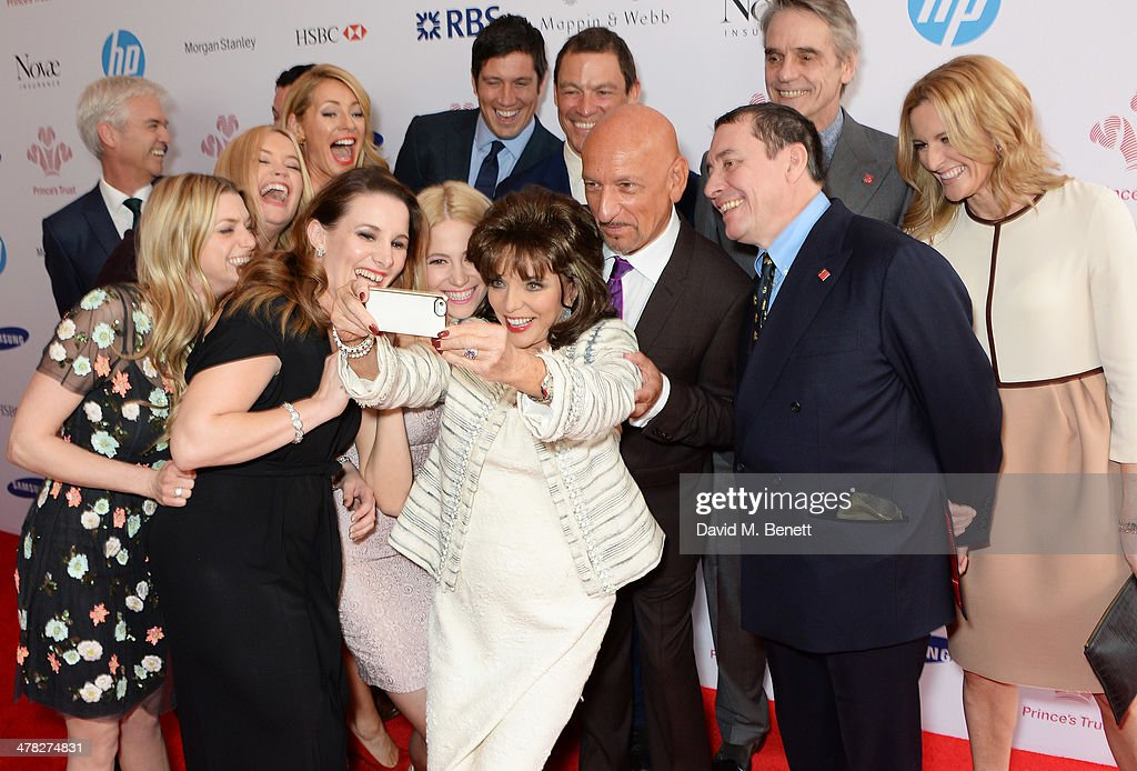Actress Joan Collins (C) takes a selfie with fellow guests including Phillip Schofield, Anna Williamson, Laura Whitmore, Tess Daly, Sam Bailey, Pixie Lott, Vernon Kay, Dominic West, Sir Ben Kingsley, Jools Holland, Jeremy Irons and Gabby Logan at The Prince's Trust & Samsung Celebrate Success Awards at Odeon Leicester Square on March 12, 2014 in London, England.