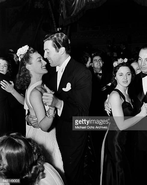 Actress Joan Crawford dances with actor Cesar Romero during an event in Los Angeles California