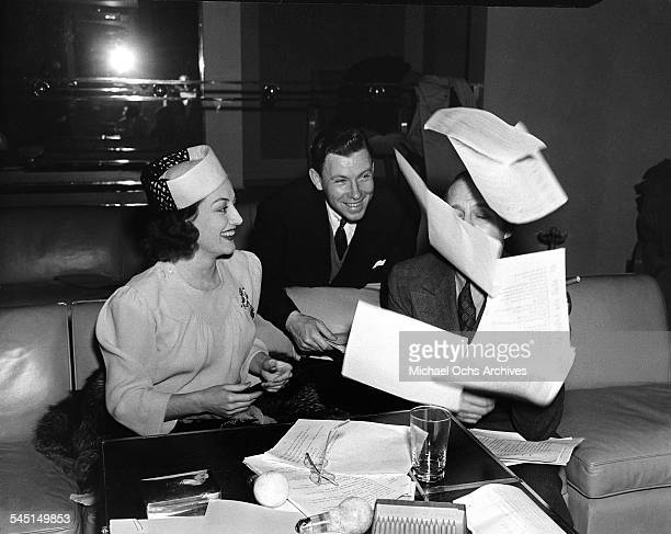 Actress Joan Crawford meets with Comedian Jack Benny as he tosses papers in Los Angeles California