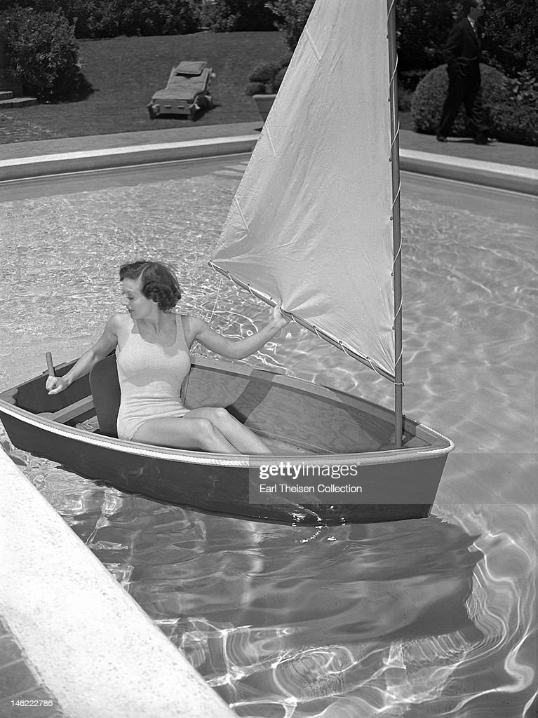 Actress Joan Crawford poses for a portrait in a miniature sailboat in her pool at home circa 1940 in Los Angeles California