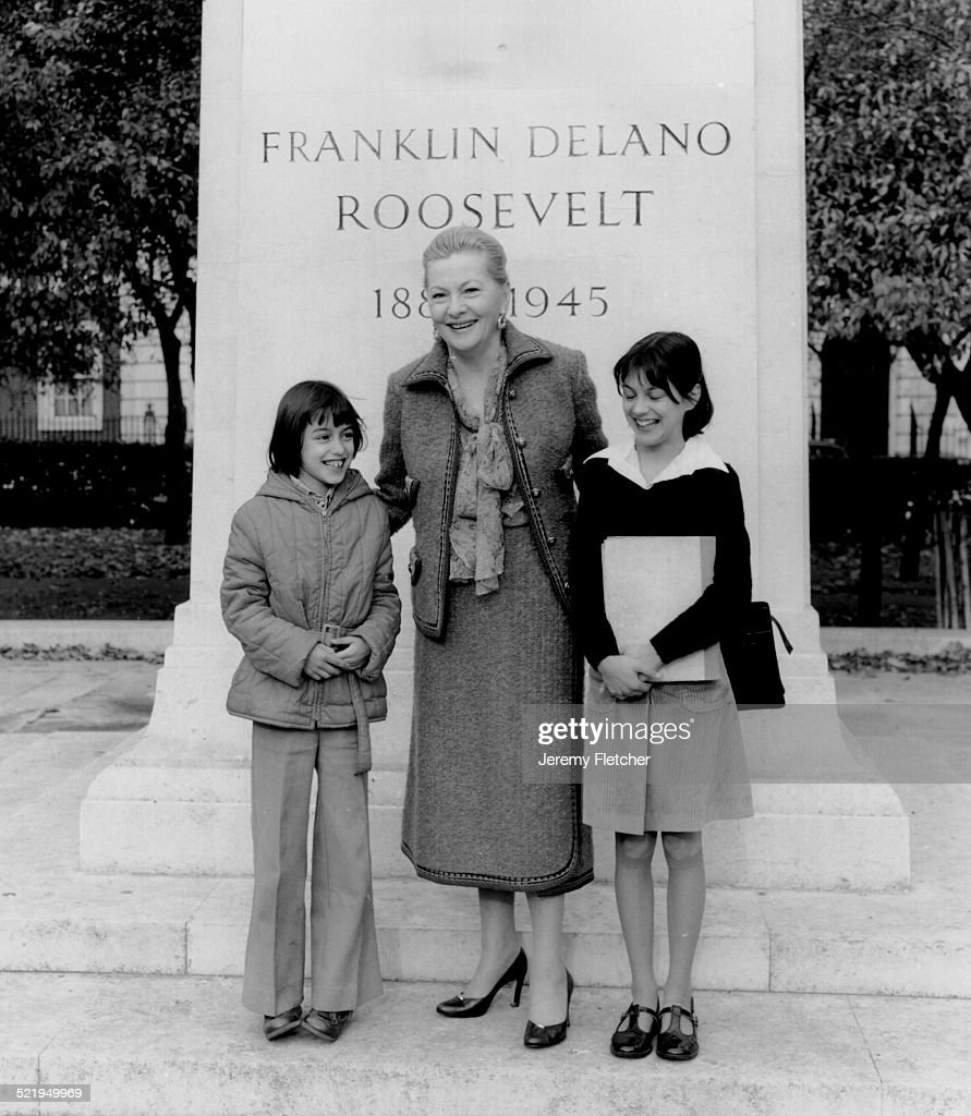 Actress Joan Fontaine (1917 - 2013) poses with two children in front of the statue of US President Franklin Delano Roosevelt in Grosvenor Square, London, 1978.