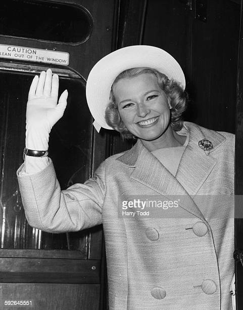 Actress Joan Regan waving farewell to Britain as she prepares to leave on a Mediterranean cruise at Waterloo Station London May 28th 1962