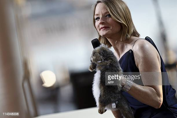 US actress Jodie Foster plays with a beaver muppet as she attends the Canal TV show 'Le Grand Journal' during the 64th Cannes Film Festival on May 17...