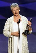 Actress Judi Dench holds her Oscar after winning for Best Performance by an Actress in a Leading Role for her part in the movie 'Shakespeare in Love'...