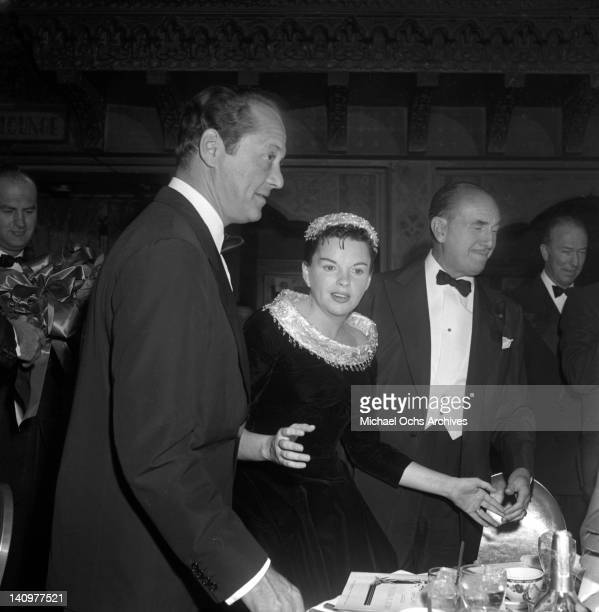 Actress Judy Garland and husband producer Sidney Luft with studio head Jack Warner attend the party celebrating the premiere of the Warner Bros film...