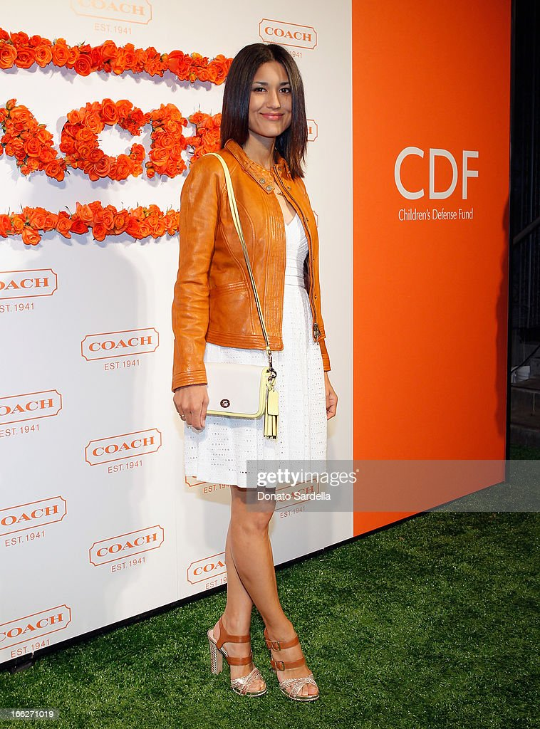 Actress Julia Jones carrying Coach attends Coach's 3rd Annual Evening of Cocktails and Shopping to Benefit the Children's Defense Fund hosted by...