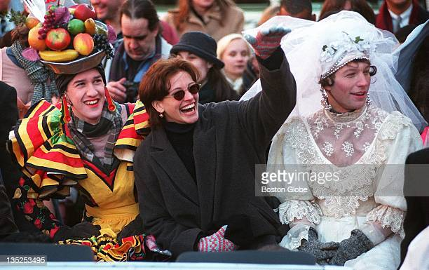 Actress Julia Roberts center is flanked by Andrew Burlinson left and Danton Char as she parades through Harvard Square on her way to the Hasty...