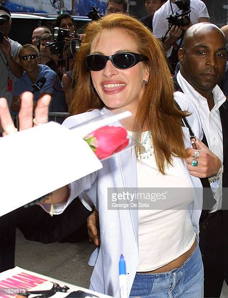 Actress Julia Roberts receives a red rose from a fan as she arrives at the Ed Sullivan Theater to appear as a guest on the Late Show with David...