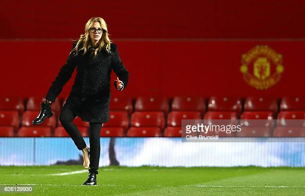 Actress Julia Roberts takes off her shoe on the pitch after the Premier League match between Manchester United and West Ham United at Old Trafford on...