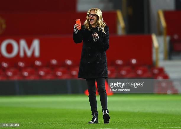 Actress Julia Roberts takes photos on the pitch after the Premier League match between Manchester United and West Ham United at Old Trafford on...