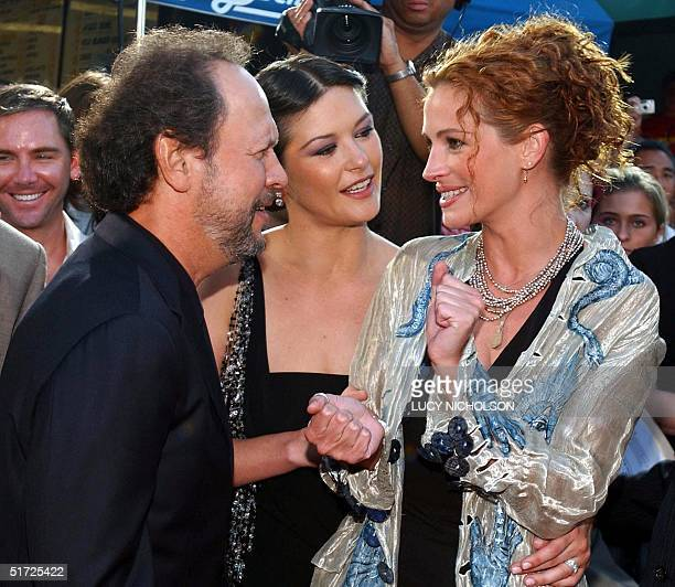US actress Julia Roberts talks to costars US actor Billy Crystal and Welsh actress Catherine ZetaJones as they arrive at the premiere of their new...