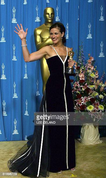 Actress Julia Roberts waves as she holds her Oscar for Best Actress for her role in 'Erin Brockovich' at the 73rd Annual Academy Awards at the Shrine...