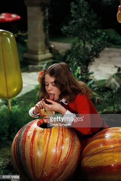 Actress Julie Dawn Cole as the character Veruca Salt takes a taste of an oversized candy on the set of the movie Willy Wonka the Chocolate Factory