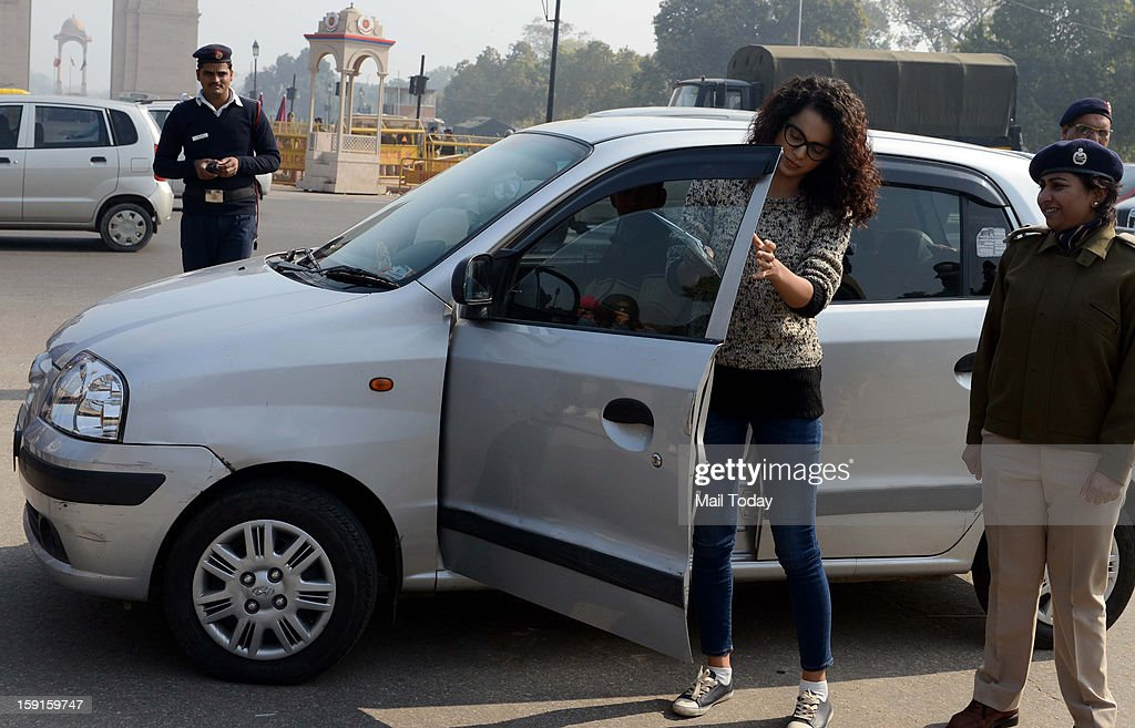 Actress Kangna Ranaut removes a black film from a car window as she takes part in an event organised by the traffic police at India Gate to mark National Road Safety Week in New Delhi on Tuesday.