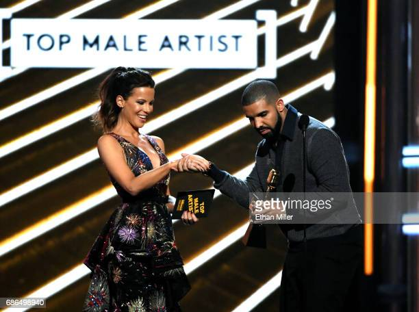 Actress Kate Beckinsale presents the Top Male Artist award to recording artist Drake onstage during the 2017 Billboard Music Awards at TMobile Arena...