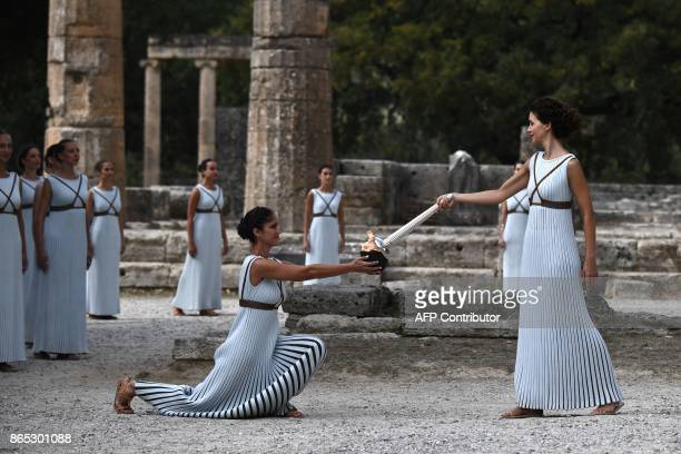 TOPSHOT Actress Katerina Lechou acting the high priestess passes the Olympic flame at the Temple of Hera on October 23 2017 during a dressed...