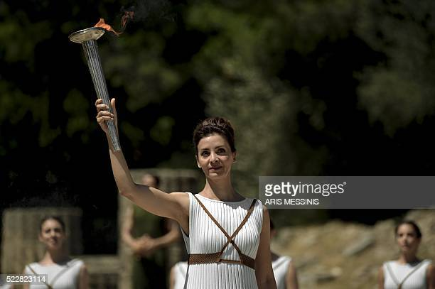 Actress Katerina Lechou performing as the high priestess holds a torch with the Olympic flame at the Temple of Hera on April 21 during the lighting...