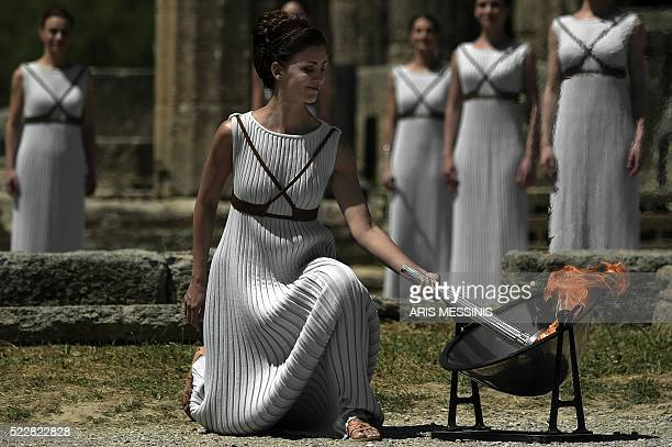 TOPSHOT Actress Katerina Lechou performing as the high priestess lights the Olympic flame at the Temple of Hera on April 21 2016 during the lighting...