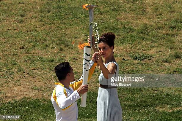 Actress Katerina Lehou who plays the role of high priestess passes the olympic flame to the first torchbearer and reigning world champion gymnast...