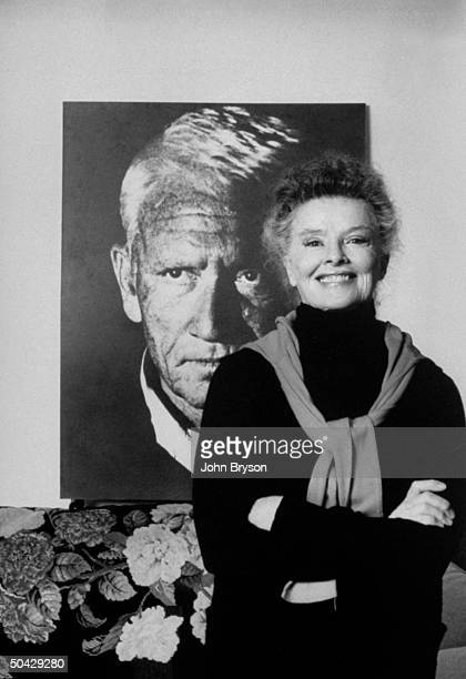 Actress Katharine Hepburn standing in front of a poster size photo of actor Spencer Tracy in her townhouse