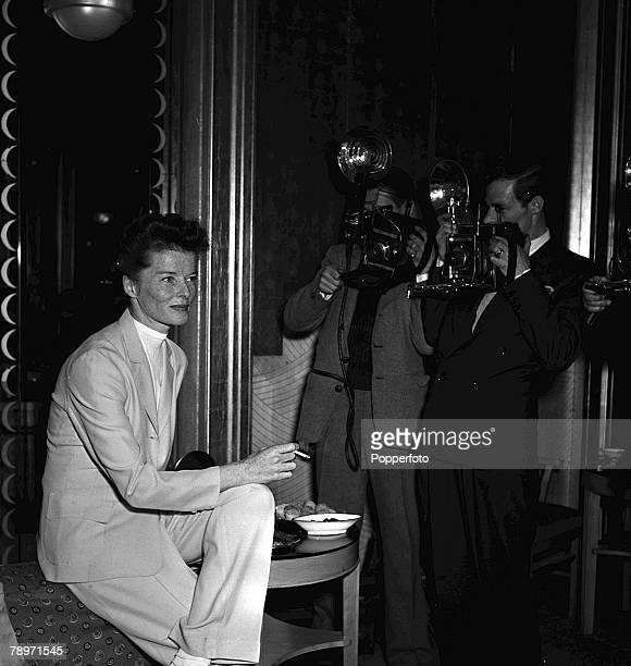 Actress Katherine Hepburn smokes a cigarette as she has her picture taken by photographers at a press reception at Claridges in London 16th April 1951