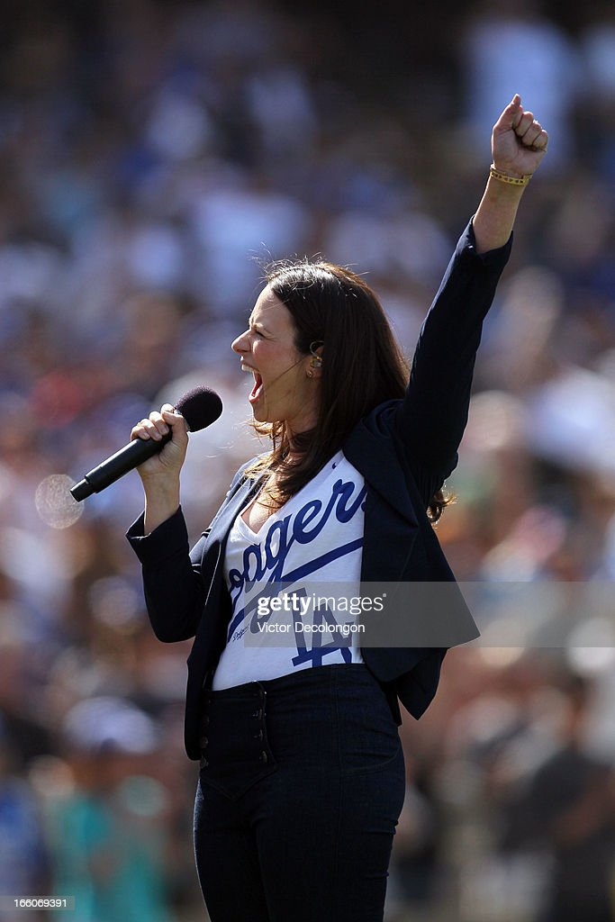 Actress Katie Lowes from the television show 'Scandal' sings God Bless America during the seventh inning stretch at the MLB game between the Pittsburgh Pirates and the Los Angeles Dodgers at Dodger Stadium on April 7, 2013 in Los Angeles, California. The Dodgers defeated the Pirates 6-2.