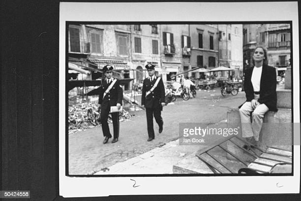 Actress Kelly Curtis sitting on fountain in the Campo dei Fiori as Italian police walk by during time off from filming movie