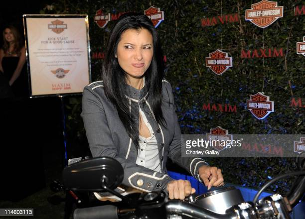 Actress Kelly Hu turns the key on a HarleyDavidson to raise money for Harley's Heroes at the 2010 Maxim Hot 100 Party held at Paramount Studios on...