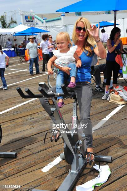 Actress Kelly Packard and her daughter Halle ride a stationary bike at the Pedal On The Pier charity event benefiting inner city schools at Santa...