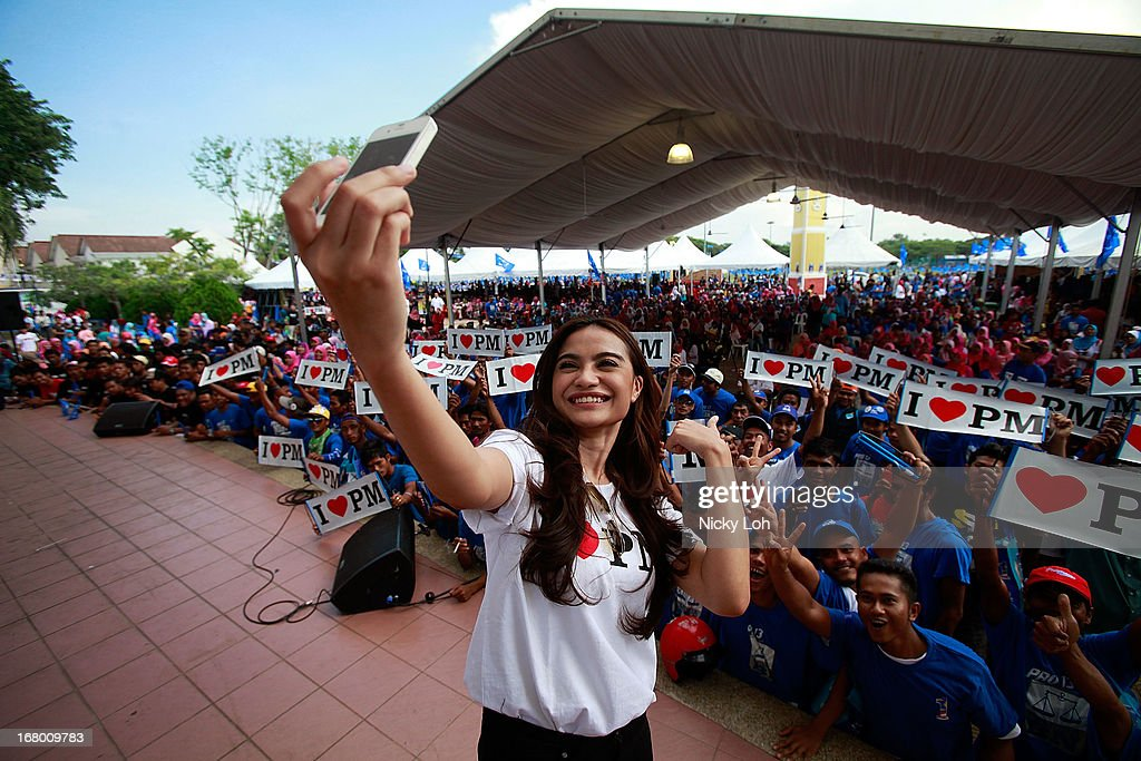 Actress Kila Fairy takes a picture with supporters while waiting for Malaysia's Prime Minister and Barisan Nasional (BN) chairman Najib Razak is blessed during an election rally to address young parliamentary constituency voters at his hometown on May 4, 2013 in Pekan, Malaysia. The election, set for May 5, will see incumbent PM Najib Razak face Anwar Ibrahim, whose opposition coalition includes moderates, Islamists and Malaysians of Chinese descent